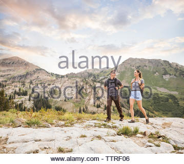 Couple talking while walking on landscape against cloudy sky in forest - Stock Photo