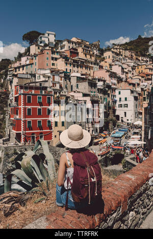 Rear view of female tourist with backpack wearing hat while looking at cityscape during sunny day - Stock Photo