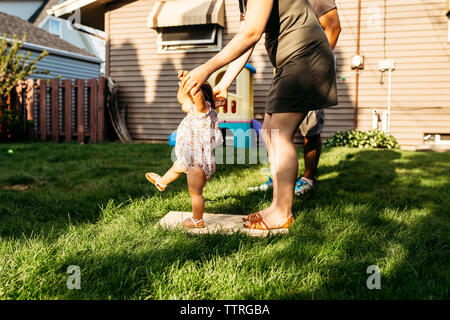 Low section of parents assisting daughter in walking at backyard - Stock Photo