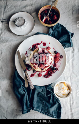 Overhead view of pancakes and syrup on table - Stock Photo