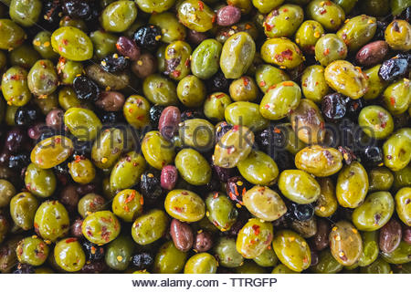 Overhead view of olives with chili flakes for sale at market stall - Stock Photo