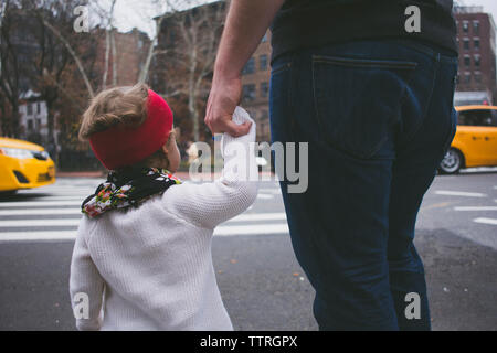 Father and daughter holding hands while crossing road - Stock Photo
