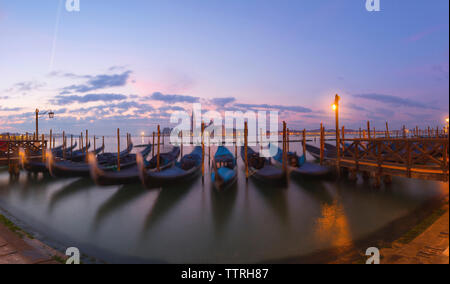 Gondolas moored on Grand Canal against sky during sunrise - Stock Photo
