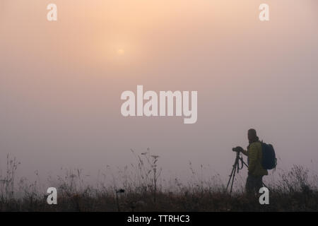 Landscape photographer taking photo in morning foggy field. Early morning foggy landscape with man silhouette - Stock Photo