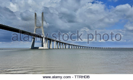 Vasco da Gama Bridge over Tagus River against cloudy sky - Stock Photo