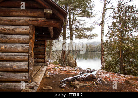 Old log cabin by lake and trees in forest - Stock Photo