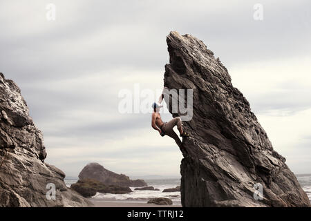 Low angle view of man climbing rock formation against cloudy sky - Stock Photo