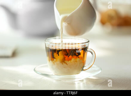 Pouring milk in tea on table - Stock Photo