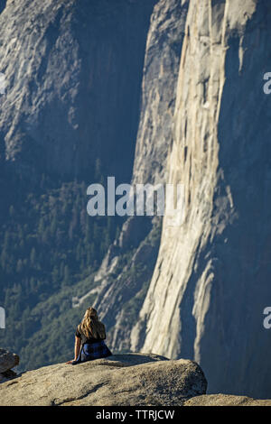 Woman sitting on cliff at Yosemite National Park during sunny day - Stock Photo