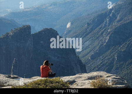 Man photographing while sitting on cliff at Yosemite National Park - Stock Photo