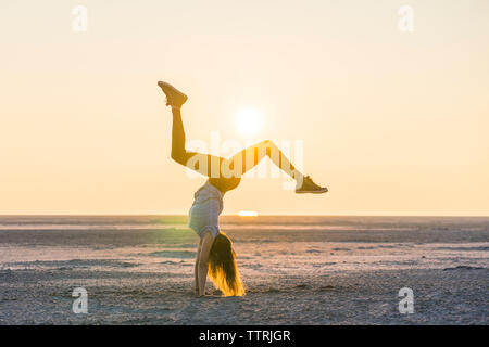 Side view of woman doing handstand at beach against clear sky during sunset - Stock Photo