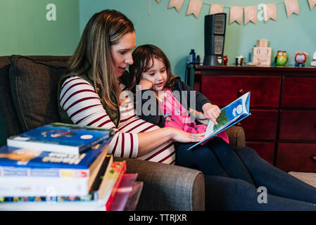 Pregnant mother with daughter reading book while sitting on armchair at home - Stock Photo