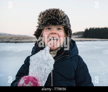 Portrait of playful girl sticking out tongue while holding ice during winter - Stock Photo