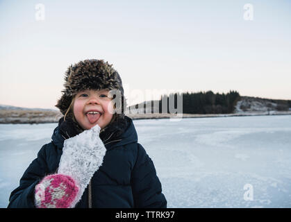 Portrait of playful girl sticking out tongue while holding ice - Stock Photo