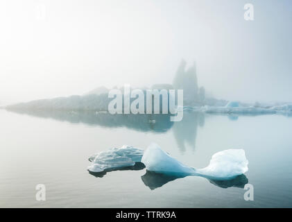 Scenic view of icebergs in sea during foggy weather - Stock Photo