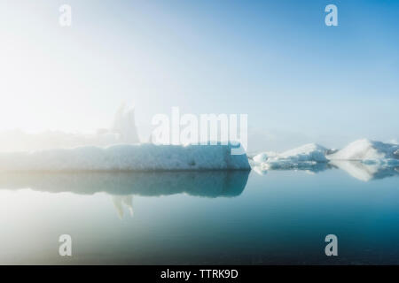 Idyllic view of icebergs in sea against sky during foggy weather - Stock Photo