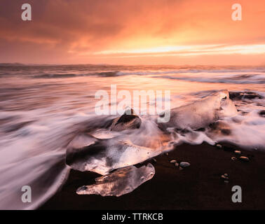 Scenic view of Jokulsarlon Lagoon against cloudy sky during sunset - Stock Photo