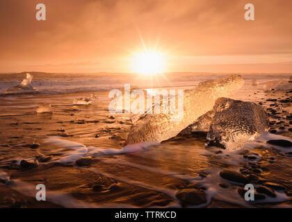 Scenic view of Jokulsarlon Lagoon against sky during sunset - Stock Photo