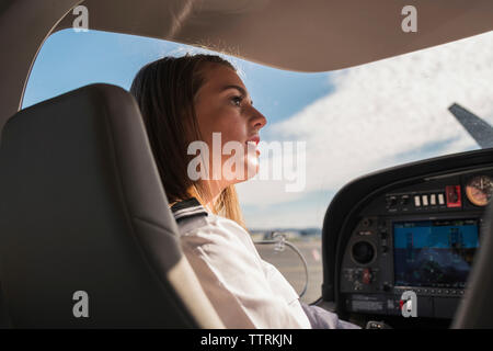 Side view of female pilot looking away while sitting in airplane at airport - Stock Photo