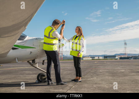 Side view of male engineer showing airplane parts to female trainee while standing against blue sky on airport runway - Stock Photo
