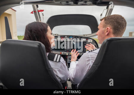 Rear view of male pilot giving training to female trainee while sitting in airplane at airport - Stock Photo