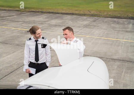 High angle view of engineer showing airplane parts to trainee while standing on airport runway - Stock Photo