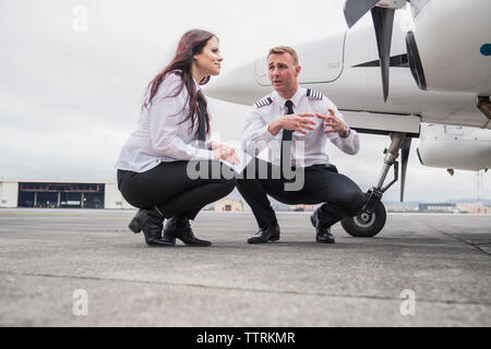 Male engineer explaining to female trainee while crouching by airplane on airport runway against cloudy sky - Stock Photo