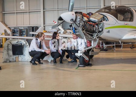 Engineer showing airplane wheel to trainees while crouching on floor in hangar - Stock Photo