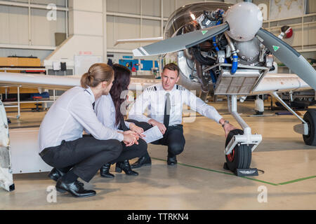 Male engineer showing airplane wheel to trainees while crouching on floor in hangar - Stock Photo