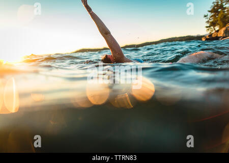 Carefree woman swimming in sea against sky - Stock Photo