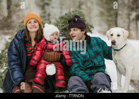 Parents with daughter and dog sitting by pine tree in forest during winter - Stock Photo