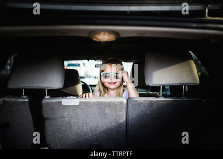 Portrait of girl wearing sunglasses while sitting in car - Stock Photo