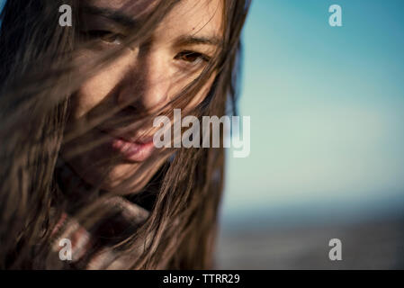 Close-up portrait of young woman with tousled hair - Stock Photo