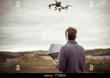Rear view of man operating drone camera while standing on field - Stock Photo