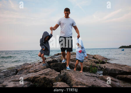 Father and children walking on rocks by sea against sky - Stock Photo