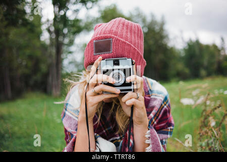 Woman photographing with instant camera on grassy field - Stock Photo
