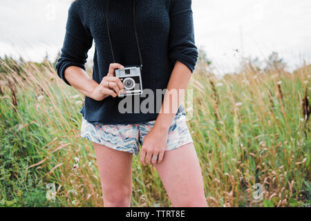Midsection of woman holding instant camera while standing on grassy field - Stock Photo