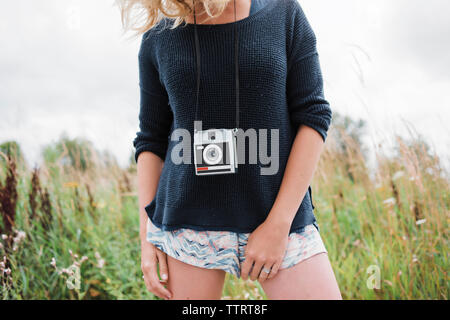 Midsection of woman with instant camera standing on grassy field - Stock Photo