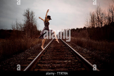 Happy woman dancing on railroad tracks against cloudy sky during sunset - Stock Photo