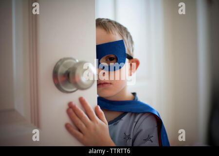 Close-up of boy in superhero costume looking away while standing by door at home - Stock Photo
