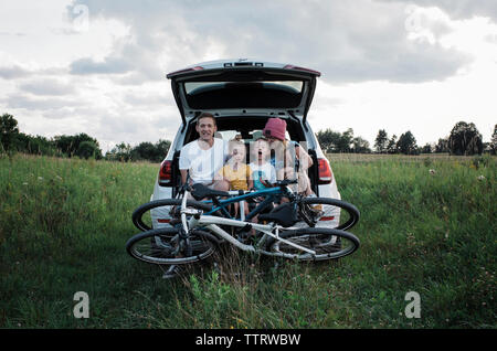 Happy family with bicycles sitting on car trunk amidst grassy field against cloudy sky - Stock Photo