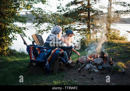 Female friends cooking marshmallows over campfire while sitting on chairs in forest - Stock Photo
