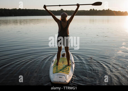 Rear view of woman with arms raised holding oar while paddleboarding on river against sky during sunset - Stock Photo