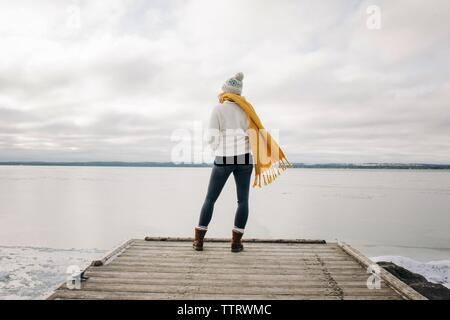woman standing on the end of a pier jetty looking out to the water - Stock Photo