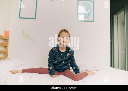 girl sitting on bed doing gymnastics playing in her bedroom - Stock Photo