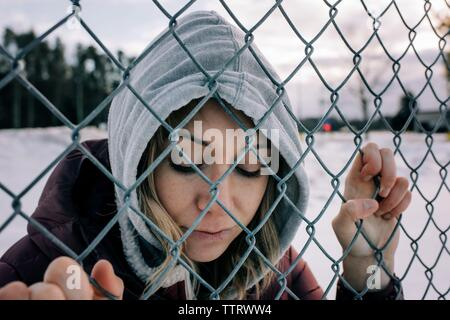 portrait of a woman holding a wire fence with her hood up in winter