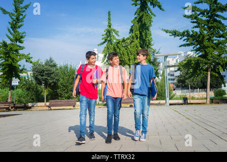 Schoolboys talking while walking on footpath against sky during sunny day - Stock Photo