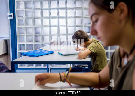 Students studying while sitting in classroom - Stock Photo