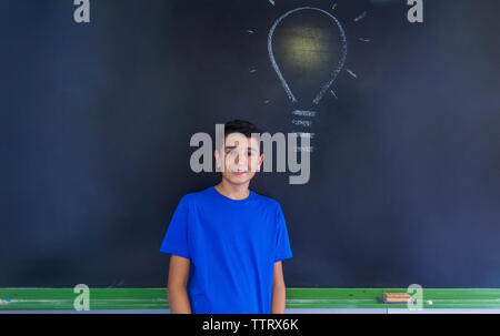 Portrait of schoolboy with light bulb drawing on blackboard standing in classroom - Stock Photo
