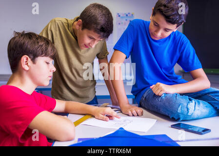 Schoolboys discussing paper in classroom - Stock Photo